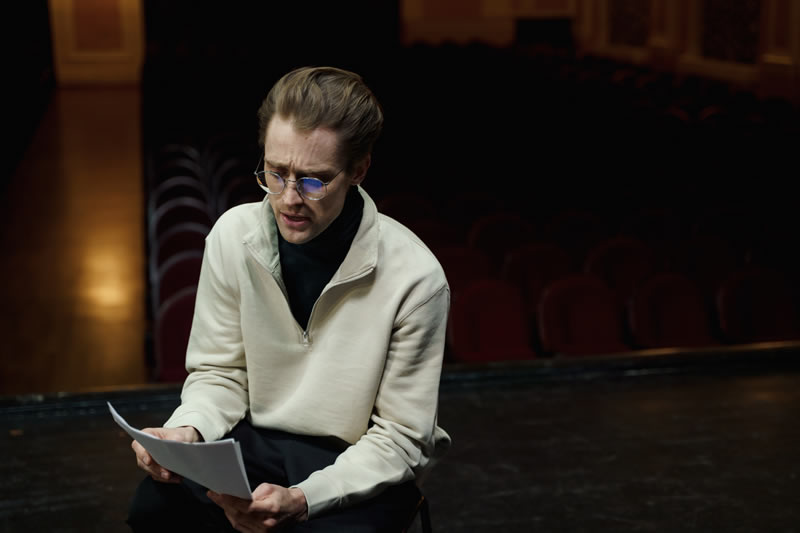 man on stage reading a script while sitting down